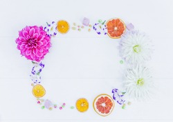 Frame of flowers and candy with dried oranges. Top view.