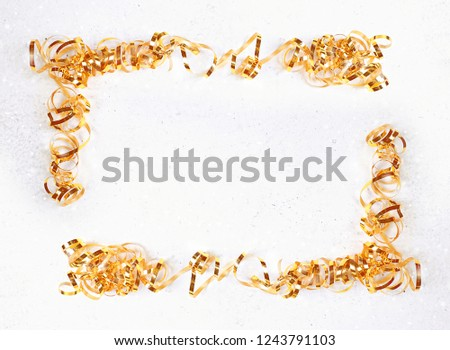 frame of gold tinsel. gold tinsel on white background. the concept of the holiday. Tinsel Christmas decoration.  top view, copy space #1243791103