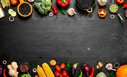 Frame of organic food. Fresh raw vegetables with black beans. On a black chalkboard.