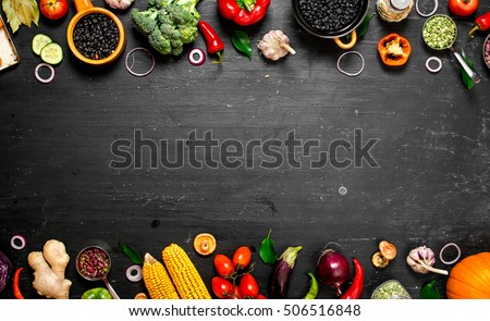 Frame of organic food. Fresh raw vegetables with black beans. On a black chalkboard. #506516848