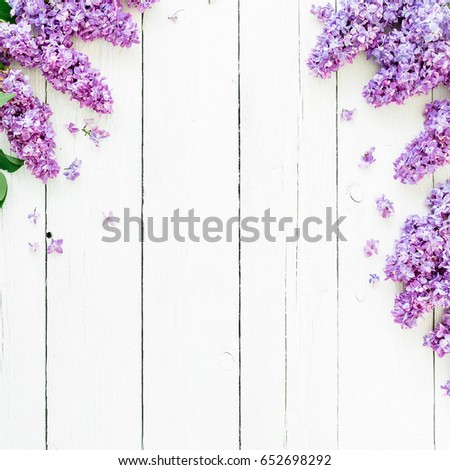 Frame of purple lilac and leaves on wooden background. Flat lay, top view. Summer pattern #652698292