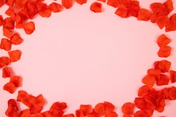 Frame of red rose leaves on pink background with copy space in center. Symbol of love on empty backdrop. Valentine sign arranged on colorful desk from directly above.