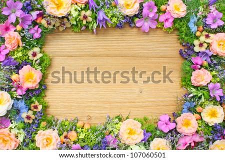 frame of summer flowers on wooden background