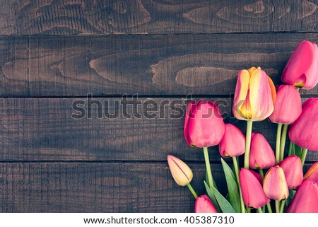 Frame of tulips on dark rustic wooden background. Spring flowers. Spring background. Valentine\'s Day and Mother\'s Day background. Top view.