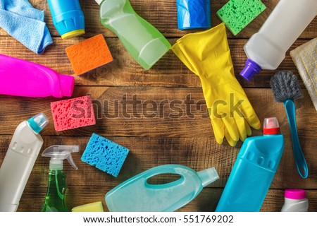 Frame of variety cleaning supplies on wooden table, top view #551769202