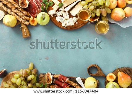 Frame of various wine snacks: grapes, peach, apricot, pear, apples, jamon, hard cheese, brie cheese and roquefort cheese on blue stone background with glass white wine top view flat lay