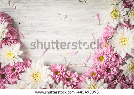 Frame of  white and pink flower on the white wooden table top view #445493395
