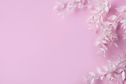 Frame of white branches with leaves on a  pink background