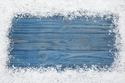 Frame of white snow on blue wooden background, top view with space for text. Christmas season