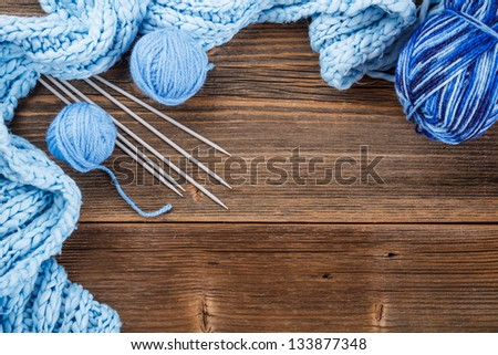 Frame of  yarn balls, knitting needles and scarf