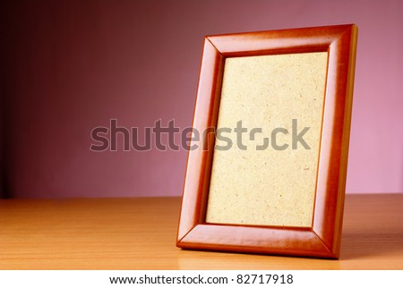frame on a wooden table and a beautiful backdrop - stock photo