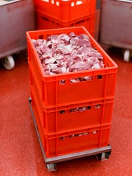 Frame picture of a many plastic red boxes with chopped fresh raw meat, a worker arranged a stored in a meat factory, industry process. Horizontal view.