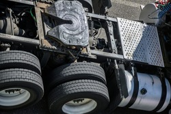 Frame with connectors and chassis with axles of a big rig semi truck tractor with double wheels with tires and a fifth wheel with a hitch with lubrication for a secure connection and smooth turns