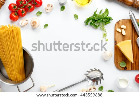 Frame with spaghetti and various ingredients for cooking pasta on a white background, top view. Flat lay