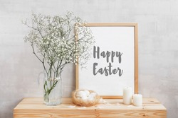 Frame with text HAPPY EASTER, glass vase with gypsophila flowers, nest with eggs, feathers and candles on a wooden table on a background of light gray walls. Easter home decor. Style room interior.