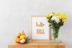 Frame with text HELLO FALL, plate with squashes (bush pumpkins) and vase with white and yellow chrysanthemums on a wooden table on a background of light gray walls. Autumn home interior decor.