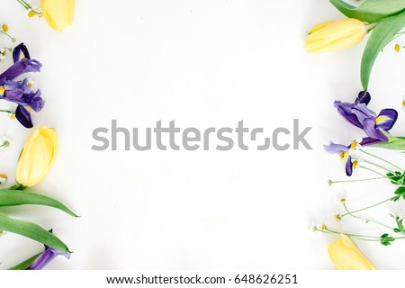 Frame with yellow tulips, purple iris and chamomile flowers on white background. Flat lay, top view. Floral background