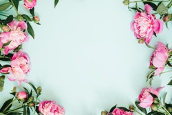 Frame wreath of pink peony flowers, branches, leaves and petals with space for text on blue background. Flat lay, top view. Peony flower texture.