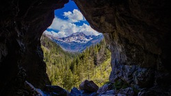 Framed mountain landscape from the inside of Mylna Cave (Jaskinia Mylna) in Koscieliska Valley in West Tatra Mountains, taken on beautiful summer day, Blyszcz and Bystra summits in the background