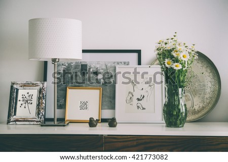Framed pictures, flowers and lamp on wooden console. Living room interior and home decor concept. Toned picture