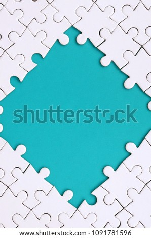 Framing in the form of a rhombus, made of a white jigsaw puzzle around the blue space #1091781596