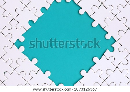 Framing in the form of a rhombus, made of a white jigsaw puzzle around the blue space #1093126367