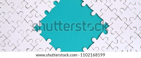 Framing in the form of a rhombus, made of a white jigsaw puzzle around the blue space #1102168199