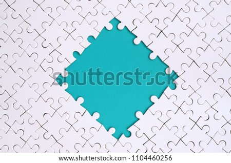 Framing in the form of a rhombus, made of a white jigsaw puzzle around the blue space #1104460256