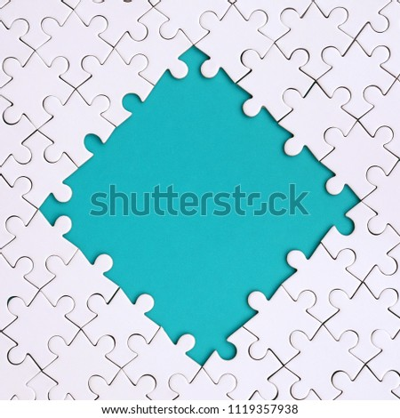 Framing in the form of a rhombus, made of a white jigsaw puzzle around the blue space #1119357938