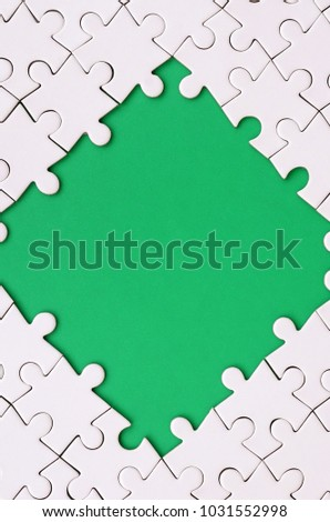 Framing in the form of a rhombus, made of a white jigsaw puzzle around the green space #1031552998