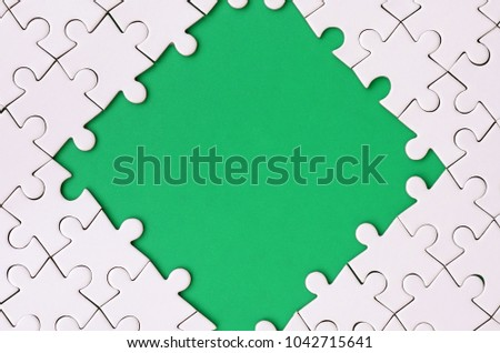 Framing in the form of a rhombus, made of a white jigsaw puzzle around the green space #1042715641