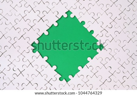 Framing in the form of a rhombus, made of a white jigsaw puzzle around the green space #1044764329