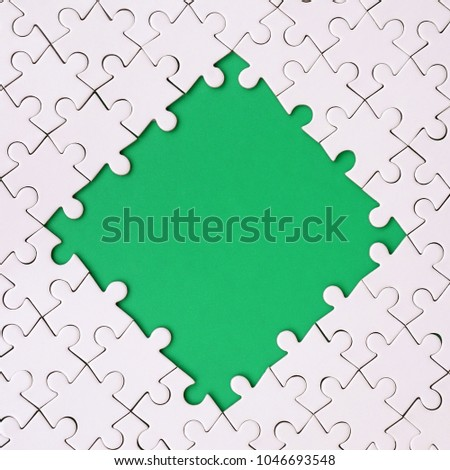 Framing in the form of a rhombus, made of a white jigsaw puzzle around the green space #1046693548