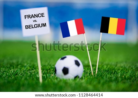 "France and Belgium national Flag on football green grass. White table with tittle ""FRANCE vs. BELGIUM"" France - Belgium, Semifinal. 11. July, Football #1128464414"