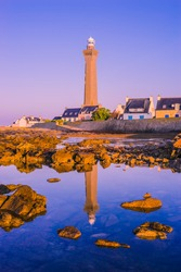 France Brittany the lighthouse of Eckmühl in the first light of the day with his reflection in the ocean