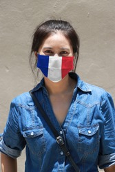 France flag on hygienic mask. Masked Asian woman prevent germs and wear denim skirt dress. concept of Tiny Particle protection or virus corona or Covid 19.
