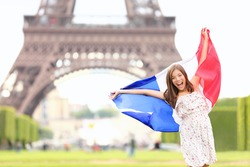 France - french flag woman by Eiffel tower, Paris. France travel concept with excited and happy young girl holding the French flag.