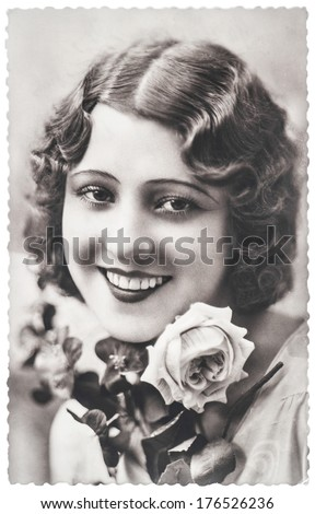 FRANCE, PARIS - CIRCA 1920: portrait of young woman with rose flowers. Typical for this period womans look