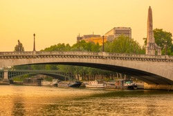 France, Paris. Summer evening over the bridges of the Seine. Residential barges are moored at the river bank