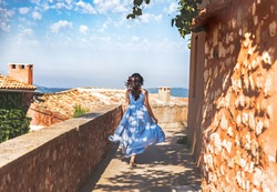 France, Provence medieval town Roussillon. French pretty young woman in blue dress with waving hair walking down the street by ancient Provencal town Roussillon. Travel and wanderlust concept.