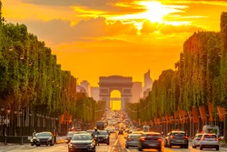 France. Summer evening in Paris. Traffic on the Champs-Elysees and the Arc de Triomphe. Golden sunset