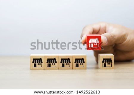 Franchise business,Businessman hand choose wooden blog with franchise marketing icons Store. Stockfoto ©