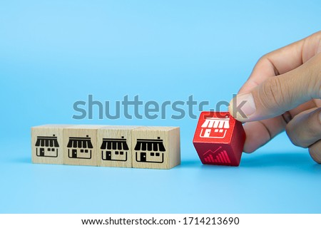 Franchise business concetps. Hand choosing cube wooden toy blog with franchise marketing store icon and graph icon. for business growth and Organizational management. Stockfoto ©