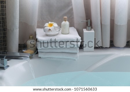 frangipani ,salt in bowl ,bottle oil on stacked of towel- interior beautiful bathroom