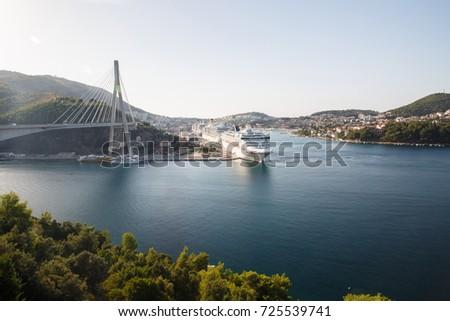 Frank Tudman's Bridge. Suspension bridge over the water in Dubrovnik and ships in the port, Croatia. #725539741