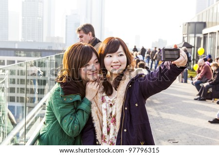 FRANKFURT - GERMANY, MARCH 5: Japanese tourists take pictures at the Hauptwache on March 05,2011 in Frankfurt, Germany. In 2010 ca. 80.660 Japanese tourists visited Frankfurt on their Germany trip. - stock photo