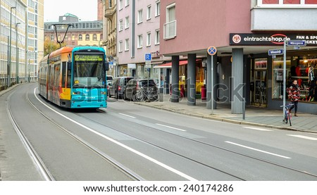 FRANKFURT, GERMANY -November 27, 2014: photo of green tram traveling in Frankfurt with an unidentified people walking nearby in cloudy day on November 27, 2014 close to Saint Bartholomew\'s Cathedral