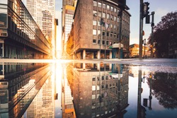 Frankfurt in the morning, looking into a street canyon with sunlight and reflection in a puddle on the street