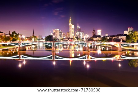Frankfurt skyline at night with lighted bridge and reflection in the water
