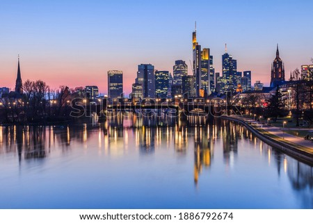 Frankfurt skyline in the evening. Sunset at blue hour with illuminated skyscrapers from the financial and business district. Reflections on the river Main with park on the bank